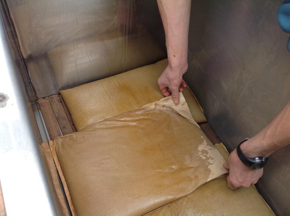 釜戸で煮た醤油を布袋に入れ、絞り機へ