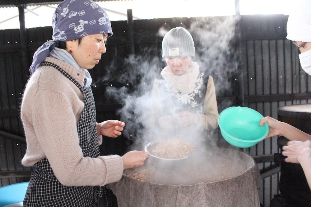 一晩水につけ、朝から釜戸で蒸してやわらかくなった大豆を桶に取り分けます