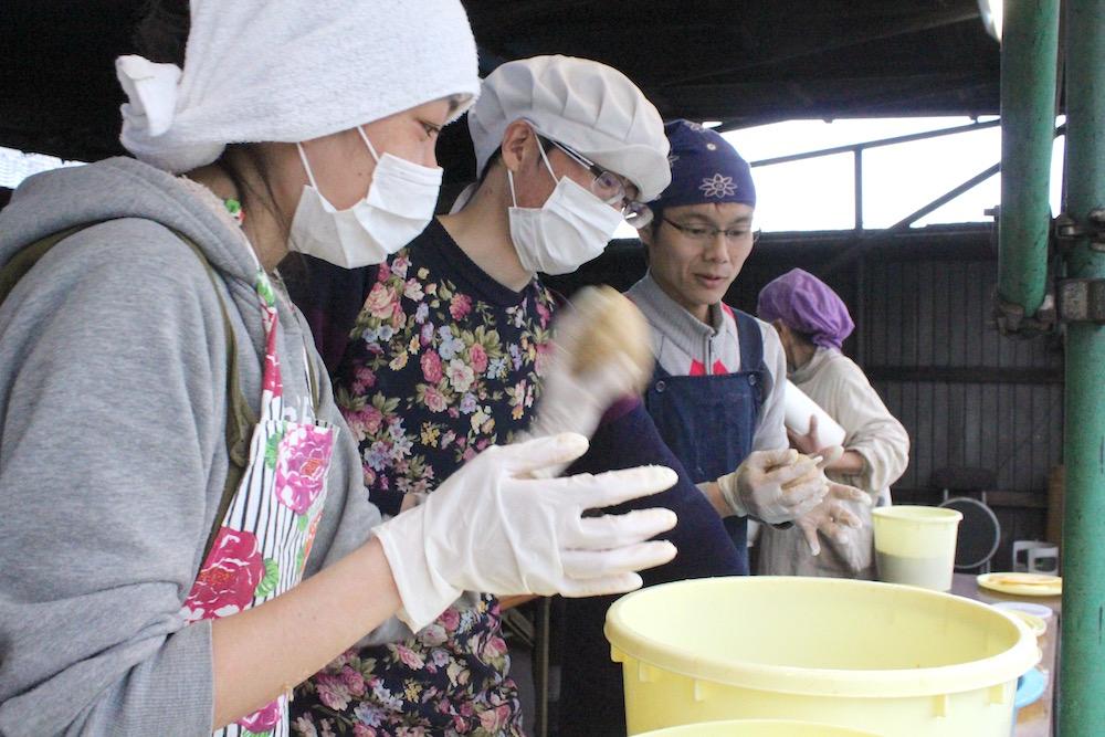 「エイッ!」と容器に投げ込んでいきます。味噌の糀菌は空気が嫌いなので、こうして空気が入らないようにするのです。